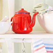 A teapot, a mortar and tea towels in a kitchen