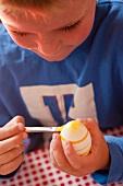 A little boy painting an Easter egg