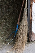 A broom and a muck rake in front of a pile of hay
