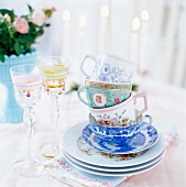 A stack of tea cups, porcelain and glasses of wine