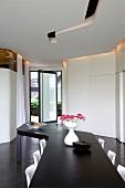 Gezackte Formen eines modernen, schwarzweissen Raumes, betont durch einen langen Esstisch und Lichtschlitze in der Decke