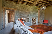 Modern interior with rustic wood-beamed ceiling and double-sided fireplace in stone partition wall