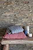 Cushions and toiletries on rough wooden bench against craggy stone wall