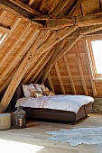 Double bed in attic under old roof structure with new wood-cladding and modern skylights