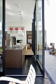 View through terrace door into modern kitchen in open-plan interior