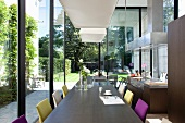 Long table and chairs with colourful upholstery in open-plan kitchen with glass walls