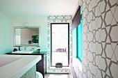 Zeitgenössisches Designerbad in Weiss und Braun mit grafisch gemusterter Retro-Tapete und türkisem Lichtspiel