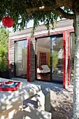 Weisser Terrassentisch mit Bank vor modernem Einfamilienhaus und klappbaren Fensterläden