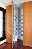 Einbau aus Holz mit offener Tür und Blick ins Bad auf WC vor gefliester Wand