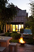 Terrace with outdoor furniture in front of lit fire bowl at twilight
