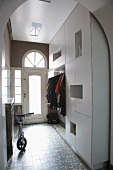 Mix of styles in entrance hall with flat-fronted, white cloakroom wardrobe and old-fashioned, glazed front door with arched transom window