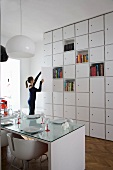 Floor-to-ceiling cupboards with several open shelf compartments in modern, white dining room