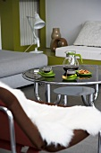 Afternoon tea - round, 70s-style coffee table with glass top and steel tube frame surrounded by various seating