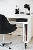 Weissglänzender Schreibtisch mit schmalen Fächern auf Rollen und schwarzer Lederdrehsessel auf weißem Dielenboden