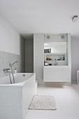Lichtgraue Fliesen im weissen, modernen Badezimmer mit eingebautem Waschtisch vor der Duschnische