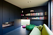 Black fitted cupboards with integrated fireplace opposite green sofa