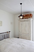 Simple bedroom with double bed and farmhouse wardrobe stained white