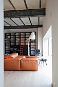 Loft apartment living room with old concrete ceiling on heavy steel joists, black, industrial-style shelving with bright orange ladder and leather couch in same shade of orange