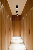 Corridor with fitted wooden cupboards and spotlights on ceiling