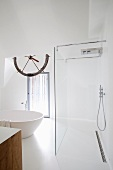 White bathroom with free-standing, round bathtub and open-plan wet area with glass partition