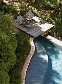 Loungers on wooden decking next to pool in Mediterranean garden