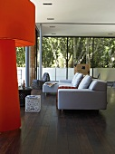 White sofa and orange standard lamp on dark parquet floor in modern living room