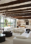 Large, open living room with curved metal wirechandeliers hanging from beamed ceiling made of unworked tree trunks