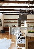 Modern mixture of styles in open kitchen-dining room with designer barstools at counter and white, 50s classic chairs with animal-skin covers at rustic table