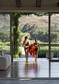 Hoher Wohnraum mit Blick in die Landschaft durch offene Fensterfront - zwei Mädchen im Bikini mit Handtüchern auf dem Weg zum Pool