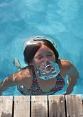 Pool with wooden walkway - girl in bikini blowing out large air bubbles underwater