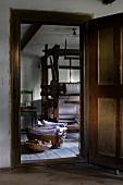 View through open door of old, wooden weaving loom and basket of laundry on floor