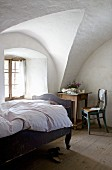 Wood-framed bed with curved foot and seating area in rustic bedroom with vaulted ceiling