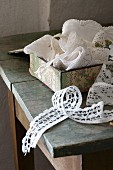 White fabric trims in vintage box on table