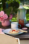 Bread and jam and small posy on rustic table in garden