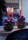 Large pine cones decorated with purple beads used as candlesticks