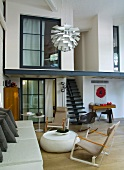 Bauhaus armchair in front of upholstered sofa and view of gallery in loft-apartment