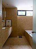 Modern bathroom with sand-coloured tiles on floor, walls, washstand and bathtub