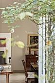 Blick von der Terrasse durch die Äste einer Kletterrose in das Wohn-/Esszimmer mit antiken Möbeln