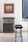 Farbenfrohe Tiermalerei über grauem, antikem Heizkörper mit Wärmefach und klassische Stahlrohr-Barhocker an einer Küchentheke