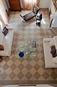Vogelperspektive auf das Schachbrettmuster eines Holzbodens in Wohnzimmer mit moderner Sitzgarnitur und einzelnen Antiquitäten