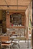 Terrasse in Naturfarben - gemauerte Kochecke und Retromöbel aus Metall unter Pergola in filigraner Stahlkonstruktion