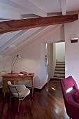 Moderner Wohnraum unterm Dach mit kleiner Schreibtischecke im Retrostil; durch farbig unterschiedlich behandelte Holzbalken betonte Dachschräge