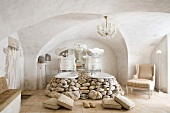 Twin bathtubs embedded in boulders in Baroque-style bathroom