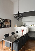 Dining table and grey, rattan basketwork chairs in modern kitchen