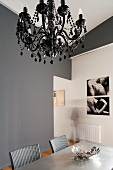 Modern dining room- black chandelier above dining area in front of grey-painted wall