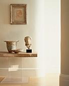 Antik griechischer Kopf aus Stein und Gefässe auf Tisch mit Steinplatte
