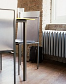 Designerstuhl aus Metall vor Ziegelwand und Fenster