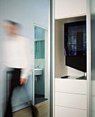 Detail of living room cupboard in open-plan living space with view through open bathroom door
