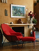 50s-style red armchair and matching footstool in front of fireplace