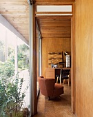 View of brown armchair in 50s-style wood-panelled living room through open door
